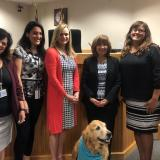 Judge Elizabeth Metzger is pictured with volunteers and court partners from the Nineteenth Circuit's Pet Therapy Dog Program.